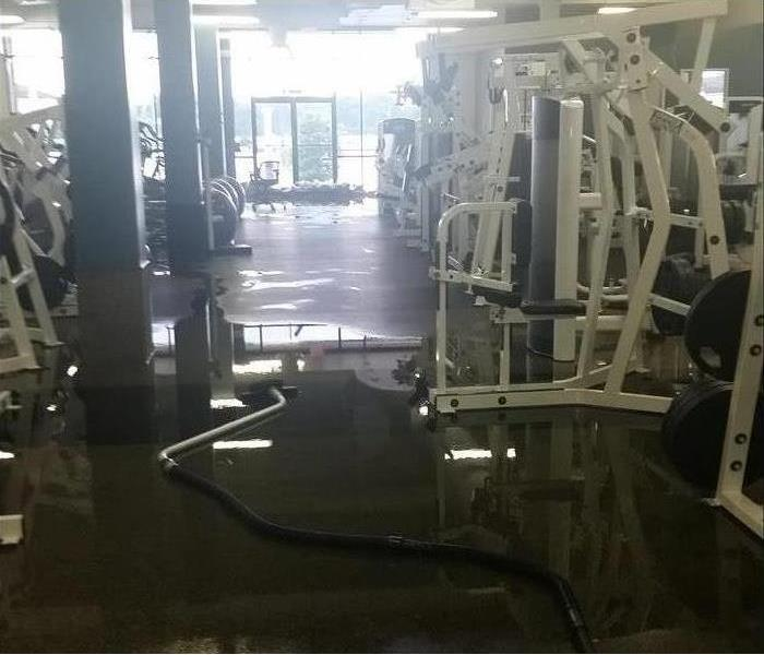 wet gym floor, hose for extracting, lots of equipment