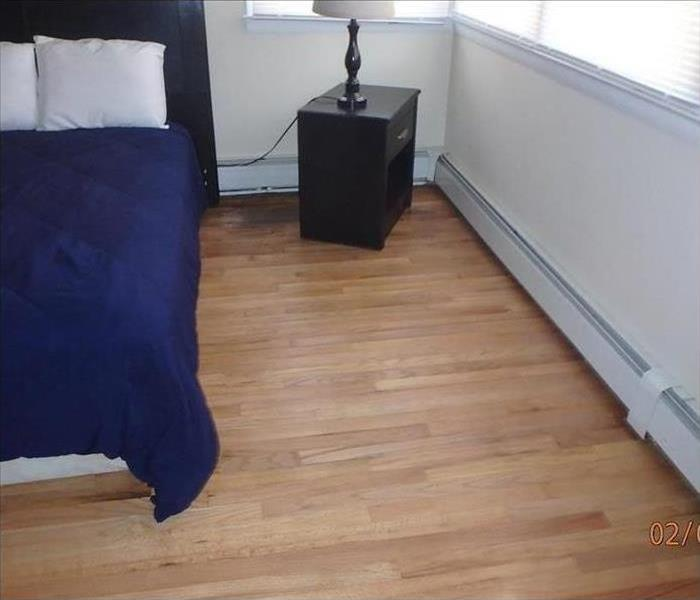 stained flooring from water leak behind nightstand