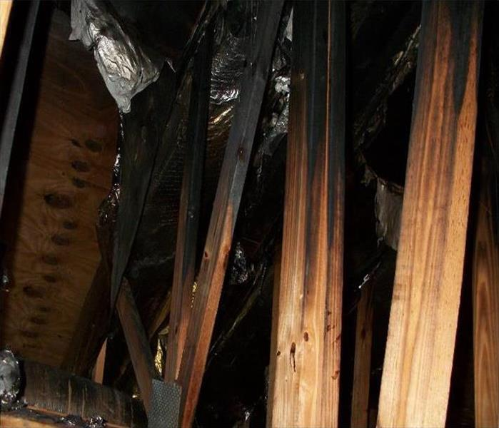 blackened roof rafters and damaged insulation from a house fire